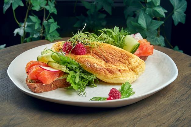 Вариант сморреброда на ржаном хлебе с омлетом, огурцами и лососем в белой тарелке на деревянной поверхности