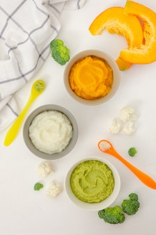 Вариант из трех домашних овощных пюре в мисках. пюре из тыквы, пюре из цветной капусты и пюре из брокколи на белом фоне.