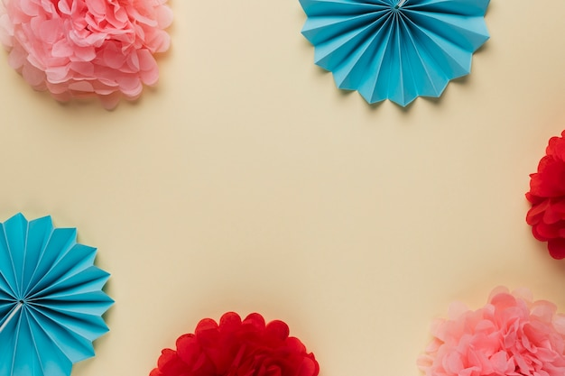 Variation pattern of beautiful colorful origami flowers arranged on beige backdrop