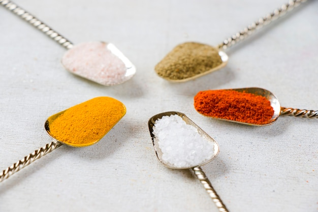 Variation of spices on the vintage silver spoons, all spices on the table, colorful food