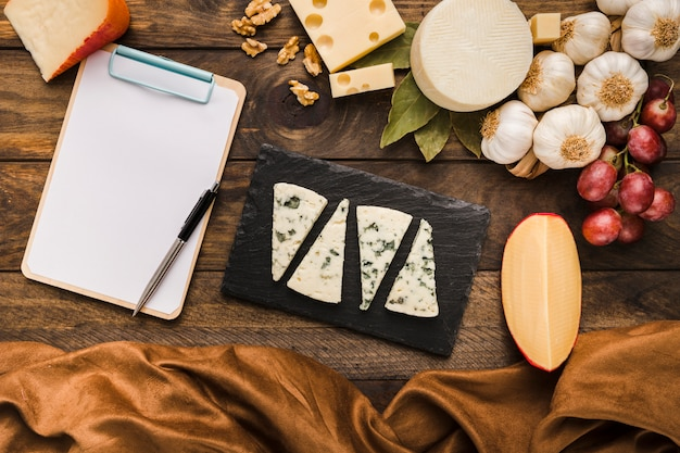 Variation of tasty cheese and healthy ingredient with clipboard over wooden backdrop