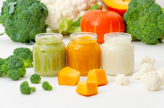 Variation of the three homemade vegetable puree in jar. pumpkin puree, cauliflower puree and broccoli puree on a white background with fresh vegetables.