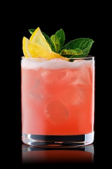 Variation of whiskey sour cocktail with grapefruit syrup isolated on black background