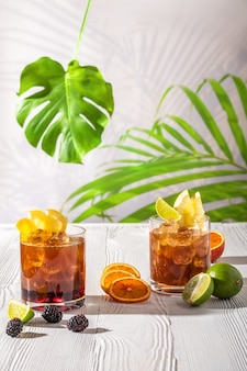 Variations of espresso-tonic refreshing drink with different fruits and syrups on wooden table under morning sun