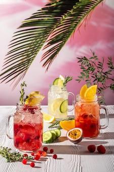 朝の太陽の下で木製のテーブルにさまざまな果物やシロップとレモネードのバリエーション