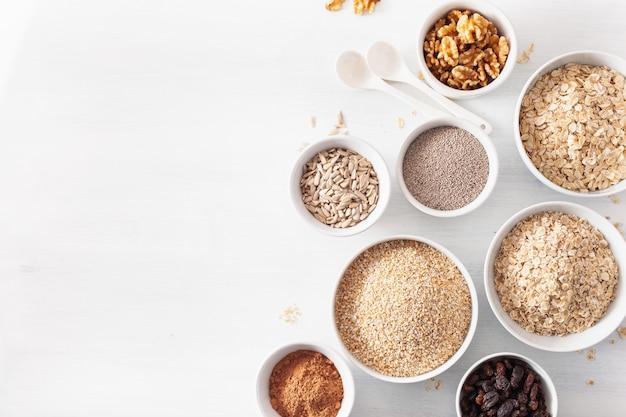 Вариаты из сырых злаков и орехов на завтрак. хлопья овсяные и стальные порезанные, ячмень, грецкий орех, чиа, изюм. полезные ингредиенты