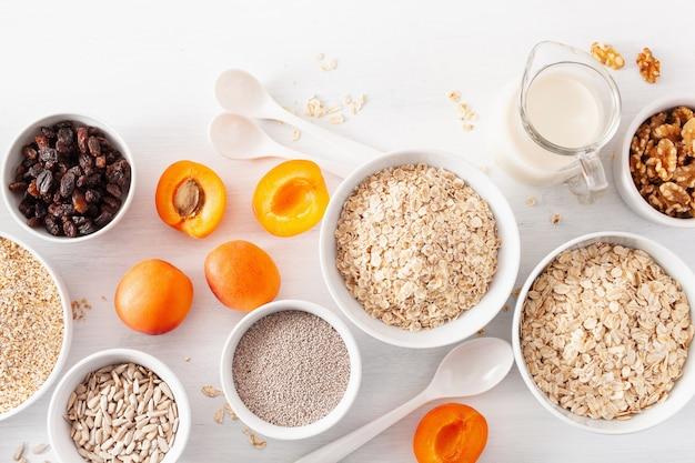 아침 식사를 위해 다양한 생 시리얼, 과일 및 견과류. 오트밀 플레이크 및 스틸 컷, 보리, 호두, 치아, 살구. 건강한 성분