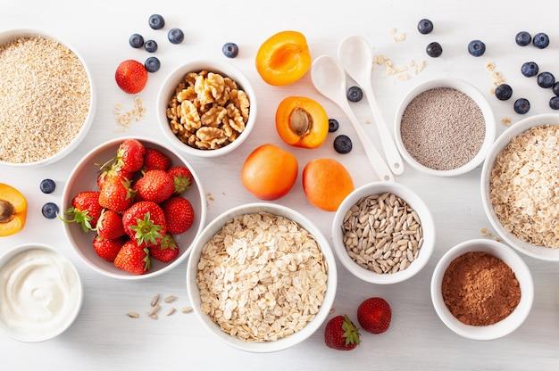 아침 식사를 위해 다양한 생 시리얼, 과일 및 견과류. 오트밀 플레이크 및 스틸 컷, 보리, 호두, 치아, 살구, 딸기. 건강한 성분