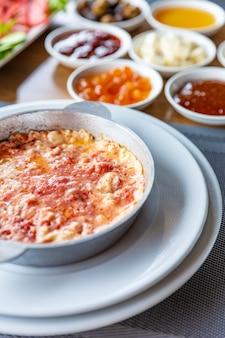 さまざまな朝食、トマトとクラシックなスクランブルエッグのスクランブルエッグのセット、さまざまな種類のスナック