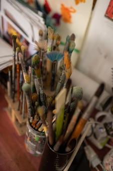 Разнообразные кисти. вид сверху на различные профессиональные кисти известного художника, стоящего на столе