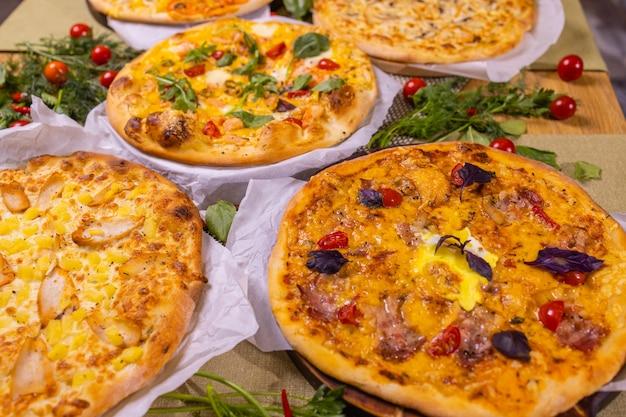 소스를 곁들인 다양한 피자. 나무 테이블에.
