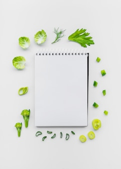Varieties of chopped vegetables surrounding spiral notepad on white backdrop
