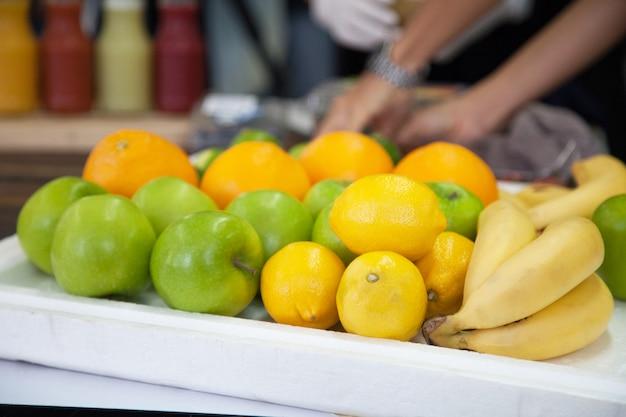 Varieties of fresh fruits (bananas, oranges, limes, apples) in market stall