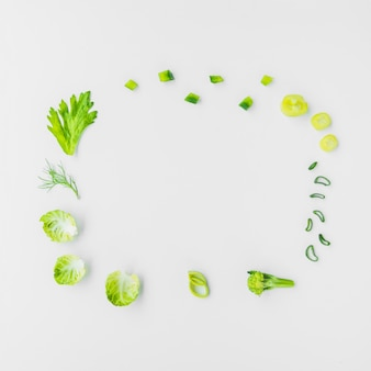 Varieties of green vegetables forming circular frame on white background