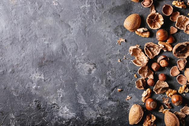 Varieties of nuts: almonds, hazelnuts and walnuts over dark texture background. top view, flat lay. copy space