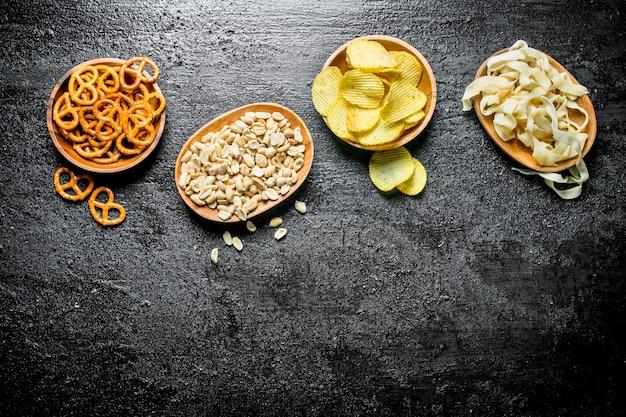Varieties of snacks in the bowls. on black rustic background
