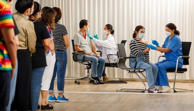 다양한 연령대의 시민들이 일렬로 서서 백신 주사를 기다리는 동안 의료인들이 마스크를 쓴 젊은 여성과 노인에게 주사합니다. 코비드-19 무리 면역 개념.