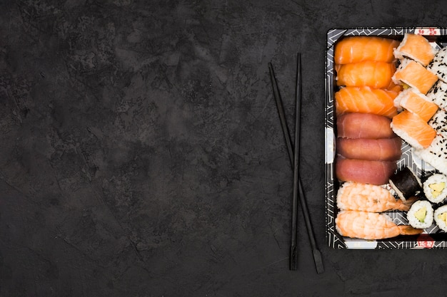 Variety of asian fish rolls on tray and chopsticks over textured background with space for text