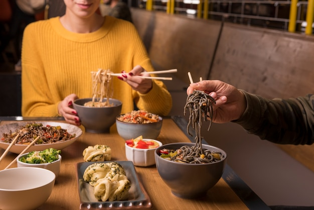 Variety of asian food and bowls of noodles on table