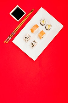 Variety of asian rolls arranged on white tray near soya sauce dip and chopsticks over red backdrop