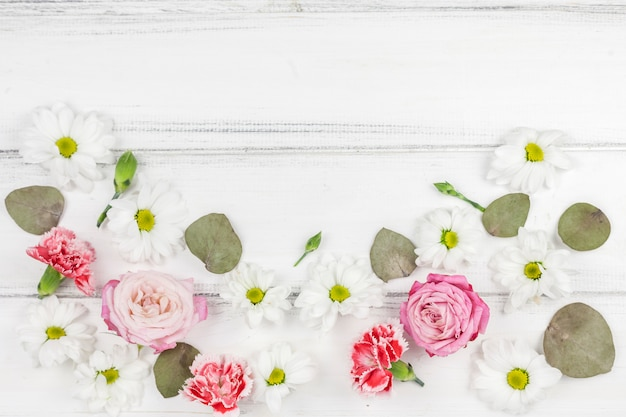 Variety of beautiful fresh flowers over white wooden desk