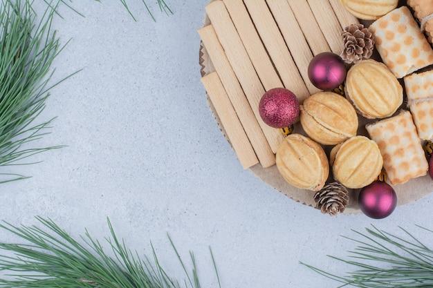 Varietà di biscotti e addobbi natalizi su tavola di legno.