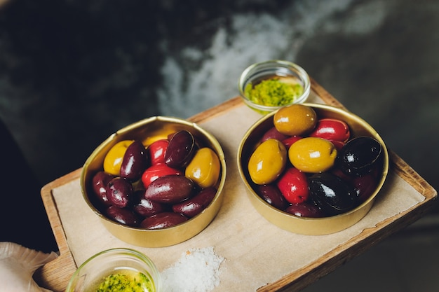 Variety of black and green olives and olive oil in bowls on white background close up.