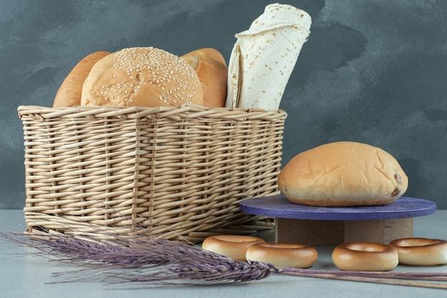 Varietà di pane in cestino e cracker sulla superficie di pietra
