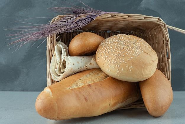 Varietà di pane in cestino e grano sulla superficie di pietra