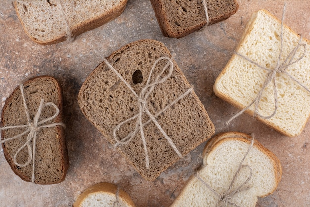 Variety of bread tied with rope on marble background