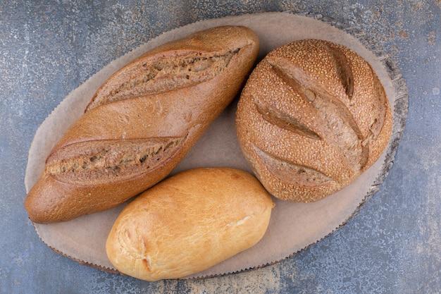 Varietà di tipi di pane su una tavola di legno sulla superficie in marmo