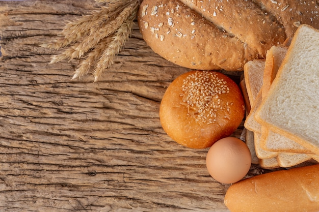 Variety of bread on wooden table on an old wooden background.