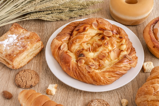 Variety of breads, croissant, pastries and wheats on wooden table surface.