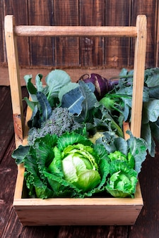 Variety of cabbages in wooden basket on brown surface,