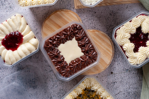 Variety of cake in the pot for delivery. strawberry, passion fruit, chocolate and coconut flavor. top view.