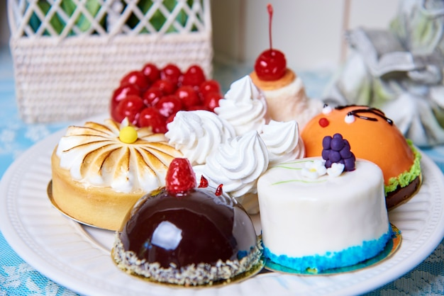 A variety of cakes on a white plate stand on a decorated table.