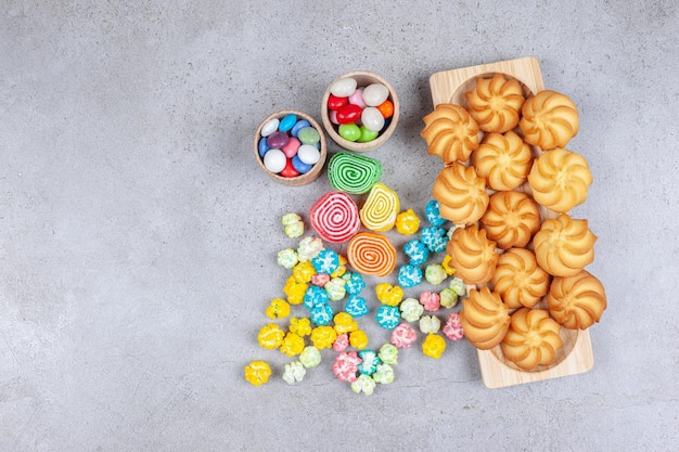 A variety of candies next to a wooden tray of cookies on marble background.
