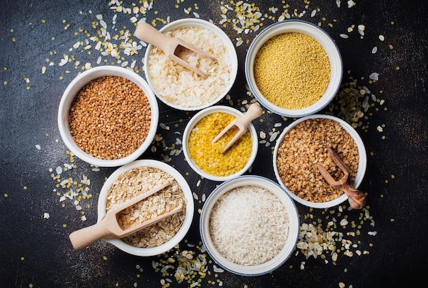 Variety of cereal flakes rice, millet, buckwheat, oatmeal. superfood in white ceramic bowls on dark old concrete