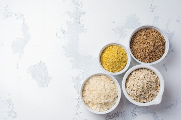 Variety of cereal flakes rice, millet, buckwheat, oatmeal. superfood in white ceramic bowls wooden