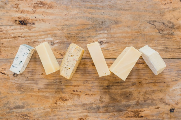 Variety of cheese blocks on wooden surface