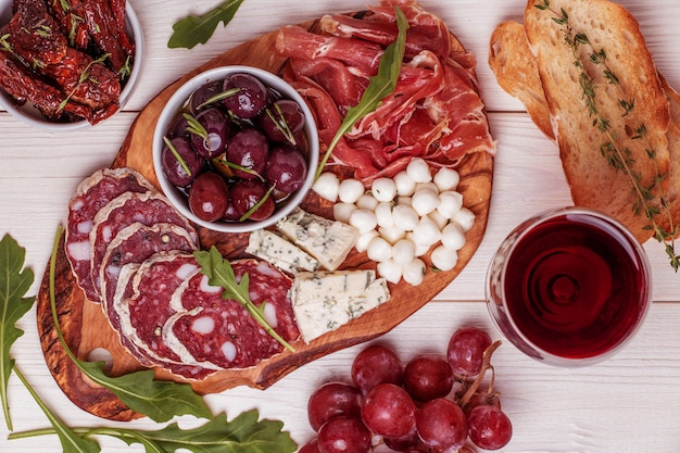 Variety of cheese and meat, olives, grapes, arugula on white table