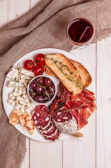 Variety of cheese and meat, olives, tomatoes on white table