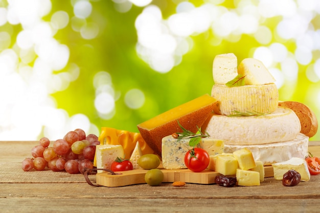 Variety of cheese types composition on wooden board