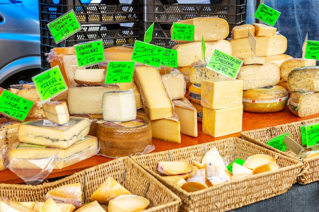 A variety of cheeses on the market counter.