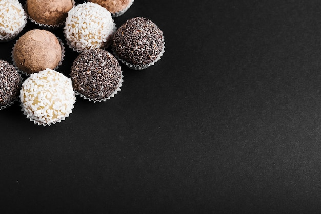 Variety of chocolate balls on black background