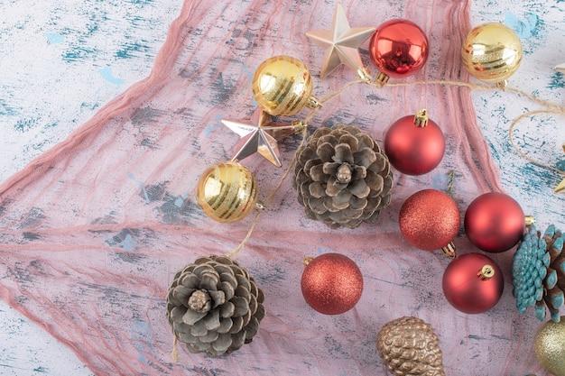 Varietà di ornamenti per alberi di natale su un pezzo di tela da imballaggio sul blu strutturato