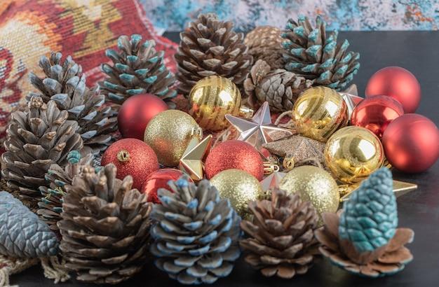 Varietà di ornamenti per alberi di natale su un pezzo di tappeto etnico con motivo rosso