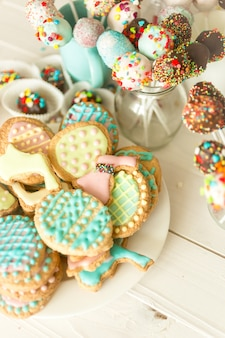 Variety of colorful cake pops and cookies on white wooden desk