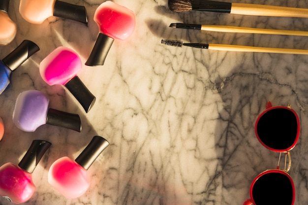 Variety of colorful lipsticks; brush; mascara; sunglasses over marble textured background