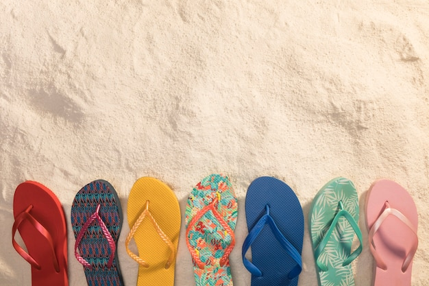 Variety of colorful thong sandals on sand